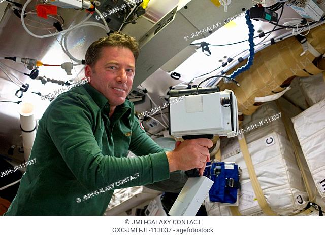 On Endeavour's middeck, European Space Agency astronaut Roberto Vittori, STS-134 mission specialist, unpacks the laser range finder