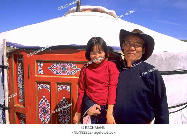 Senior man carrying his granddaughter, Ulan Bator, Independent Mongolia