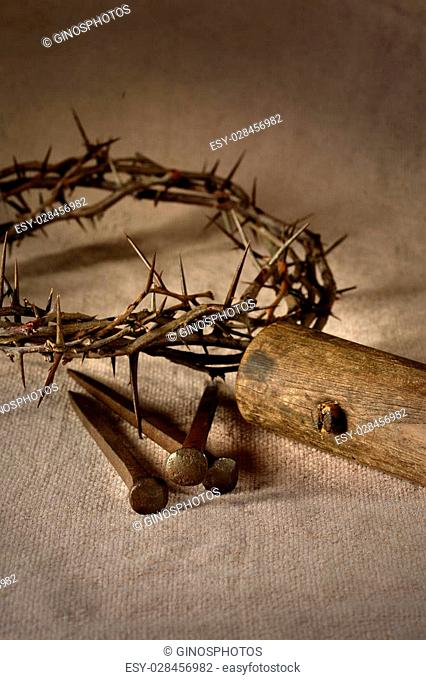 Crown of thorns, nails and wooden mallet over cloth