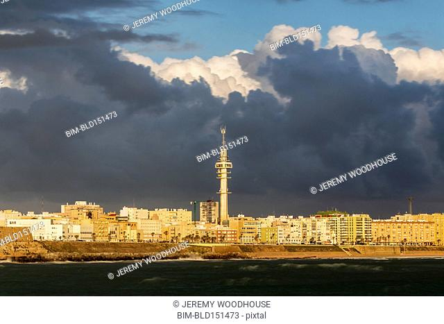 Storm clouds over tower, waterfront and Cadiz cityscape, Andalusia, Spain