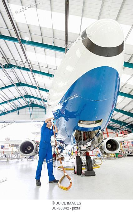 Engineer working on passenger jet in hangar