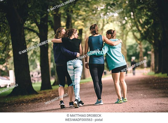 Four female joggers in park