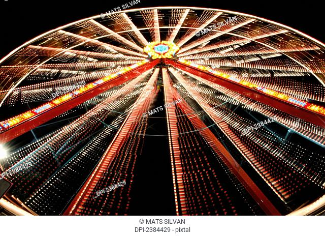 Ferris wheel glowing and spinning at nighttime; Locarno, Ticino, Switzerland