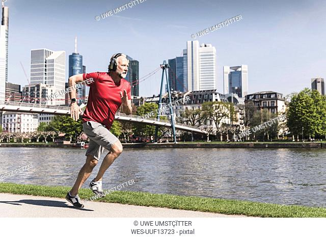 Mature man with headphones running at the riverside in the city