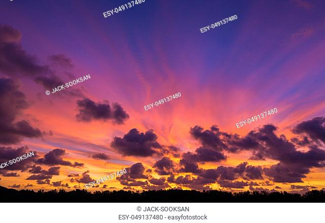 Dramatic colorful twilight sky with windy storm clouds near land covered by dark trees at the beach of Phuket, Thailand