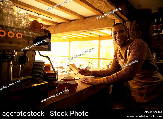 Portrait happy male coffee shop owner working behind counter