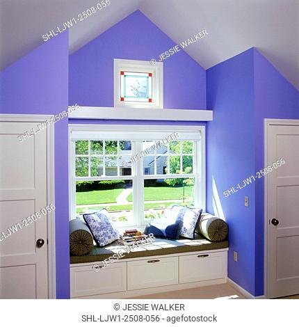 WINDOW SEAT - Window seat with storage drawers below, flanking closets, small stained glass window above larger window, cornflower blue walls, white trim