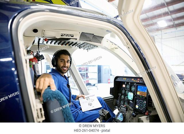Portrait confident mechanic in helicopter cockpit