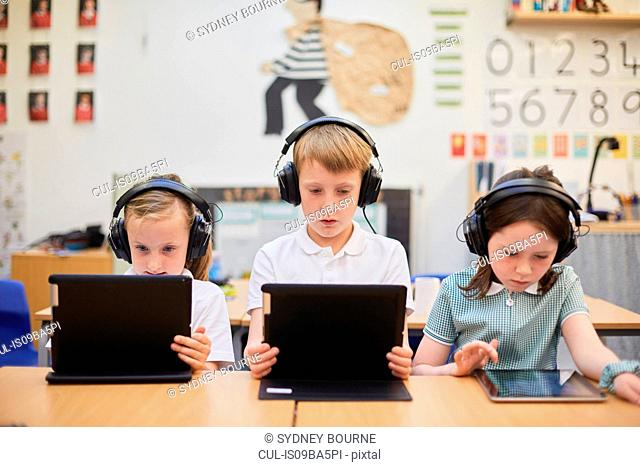 Schoolboy and girls listening to headphones in class at primary school