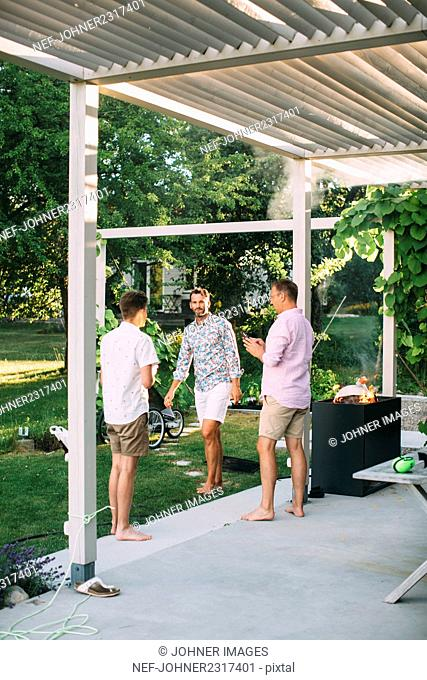 Men barbecuing in garden