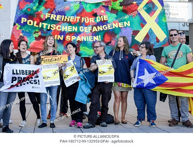 12 July 2018, Germany, Hamburg: Activists at the Jungfernstieg in Hamburg holding Catalonian flags and a banner with the words 'Freiheit fuer alle politischen...