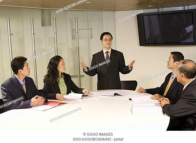 Businessman standing up in a meeting