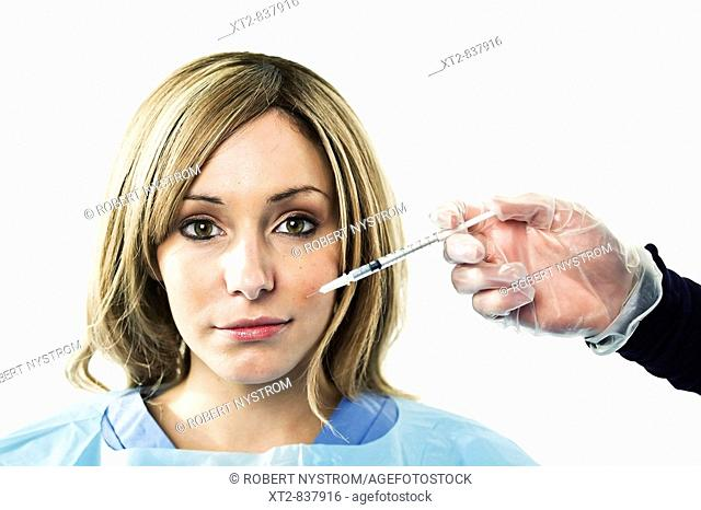 A young woman is injected with a syringe containing botox