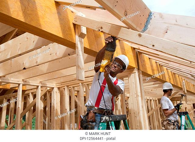 Carpenter using a sawzall on the roof boards of a house under construction