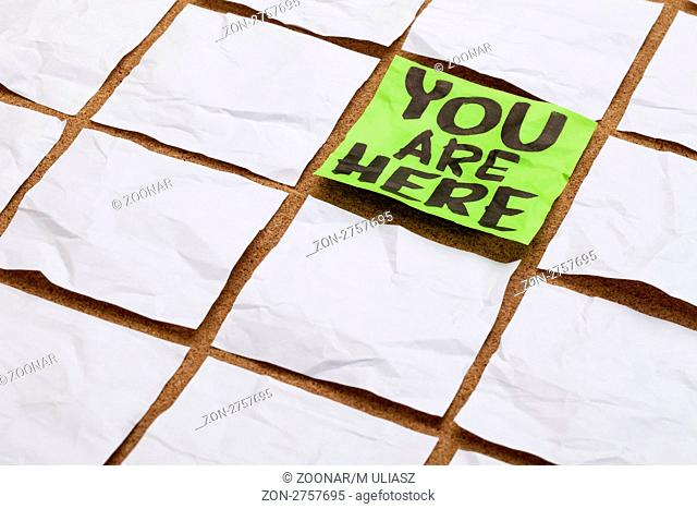 you are here concept - handwriting on a green sticky note surrounded by blank white ones