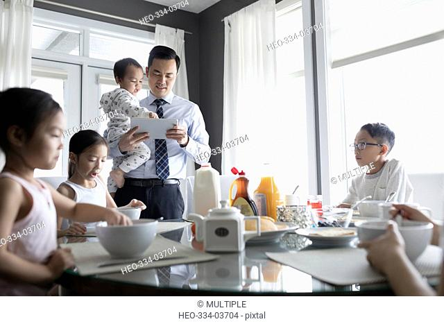 Businessman father with digital tablet and children eating breakfast at dining table