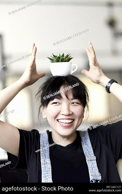 Korean woman balancing a cup with leaves on her head