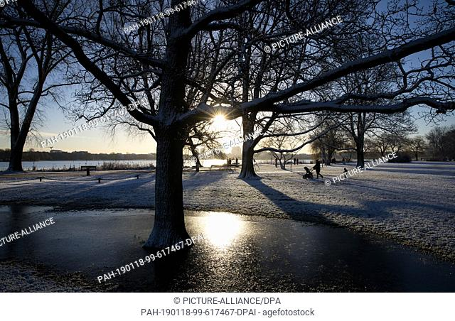 18 January 2019, Hamburg: Walkers and joggers can enjoy the bright sunshine on the snow-covered Alster meadows along the Alster