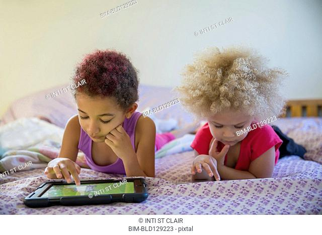 Mixed race sisters using digital tablets in bed