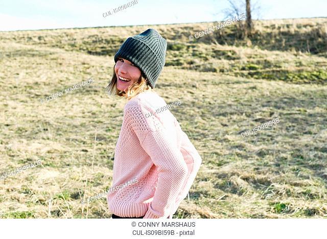 Portrait of mid adult woman wearing knitted hat in field