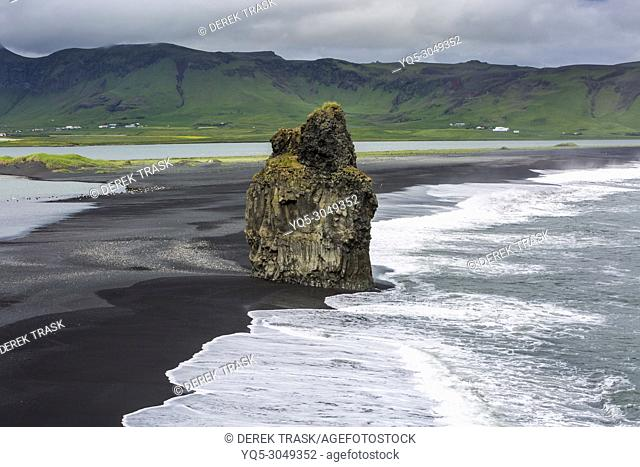 The Black Beach near Vik, Iceland, Arnardrangur or 'Eagle Rock', eagles nested there until 1850, Reynisfjara black sand beach created by lava flowing into the...