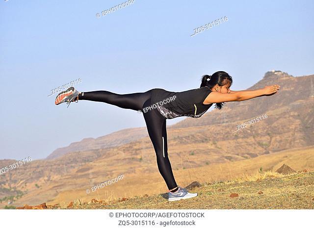 Young Indian Girl doing Yoga. Warrior Pose ,Virabhadrasana Mountain background Pune, Maharashtra