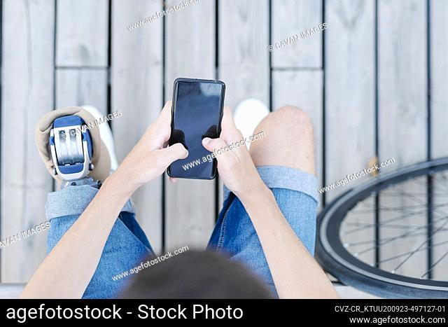 Teen male with leg prosthesis sitting on bench and browsing smartphone
