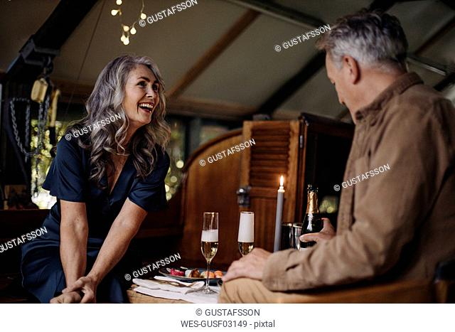 Happy senior couple having a candlelight dinner on a boat in boathouse