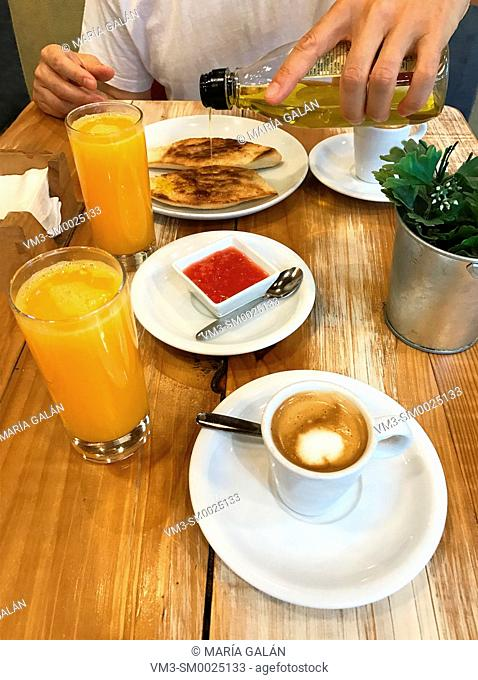 Having Spanish breakfast: orange juice, cup of coffee and olive oil on toast with tomato. Spain