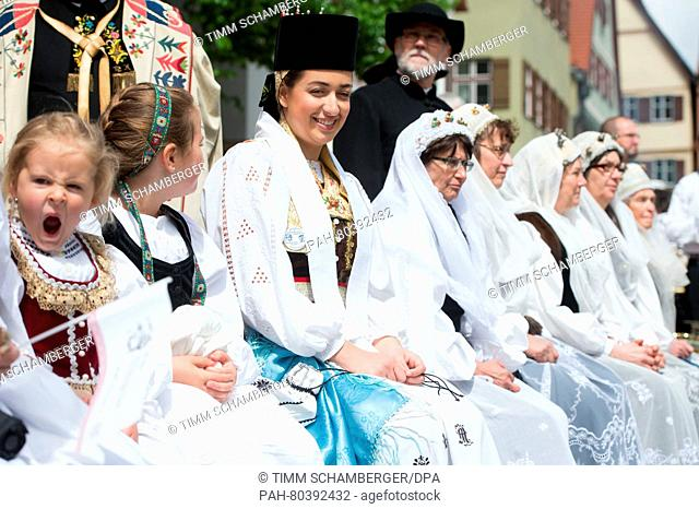 A group in traditional costume sits on a bench during the Transylvanian Saxons Pentecost meeting in Dinkelsbuehl, Germany, 15 May 2016