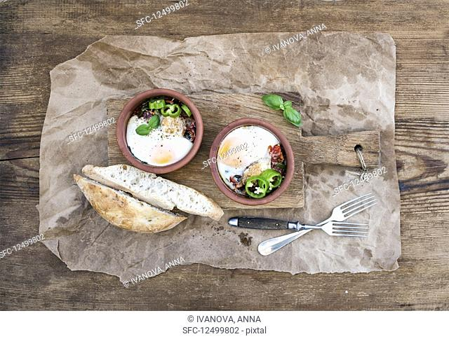 Country style breakfast - Eggs baked in clay cups with tomatoes, peppers, fresh basil and bread slices