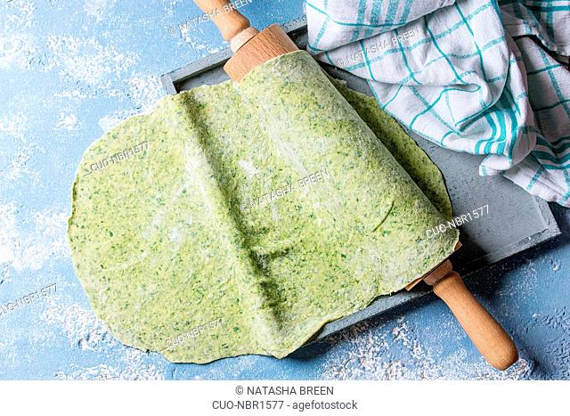 Fresh homemade green spinach rolled dough for pasta tagliatelle on wood rolling pin with kitchen towel over light blue concrete background. Top view