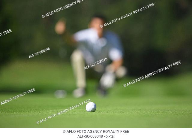 Golf ball in foreground as man lines up a putt