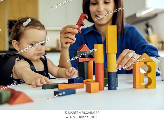 Happy mother and baby daughter playing with building blocks