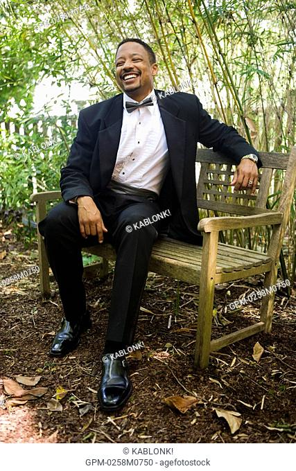 Happy African American groom sitting on outdoor bench on wedding day