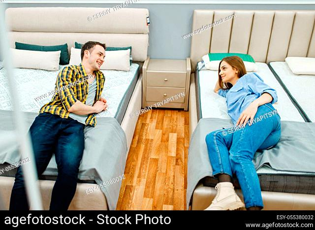 Young love couple lying in bed in furniture store showroom. Man and woman looking samples for bedroom in shop, husband and wife buys goods for modern home...
