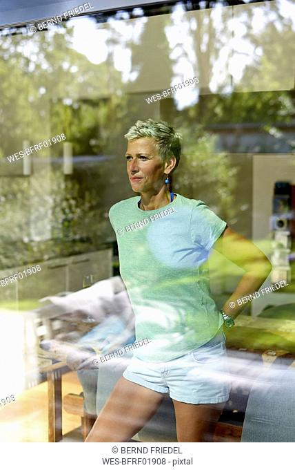 Portrait of woman with short hair looking out of window