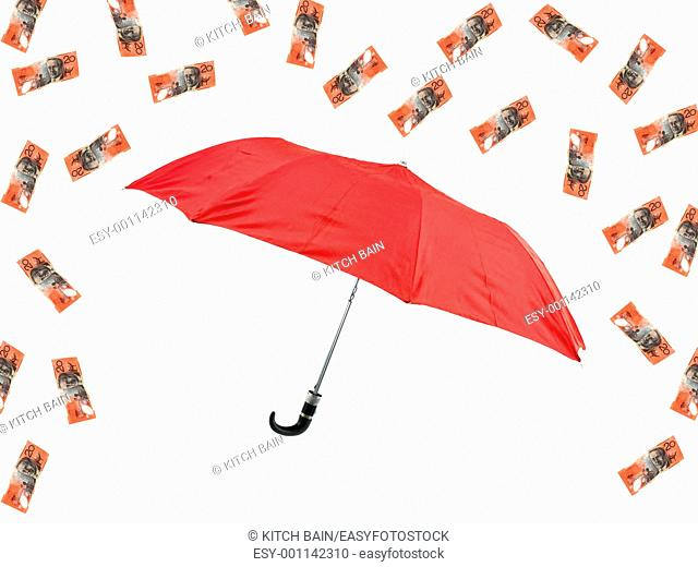 A red umbrella and cash isolated against a white background