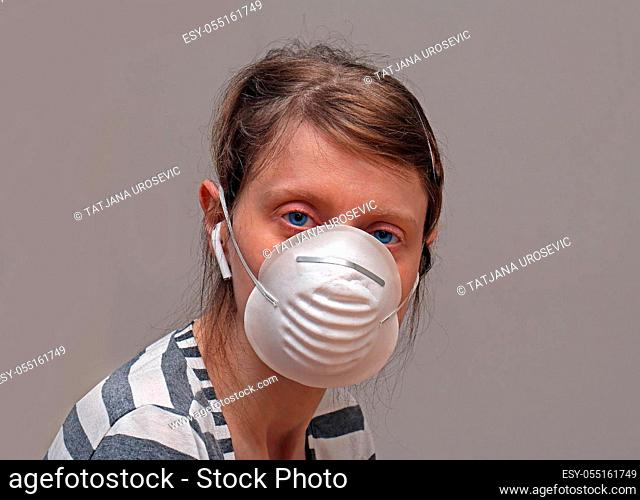 Young woman wearing face mask covering mouth and nose as virus protection