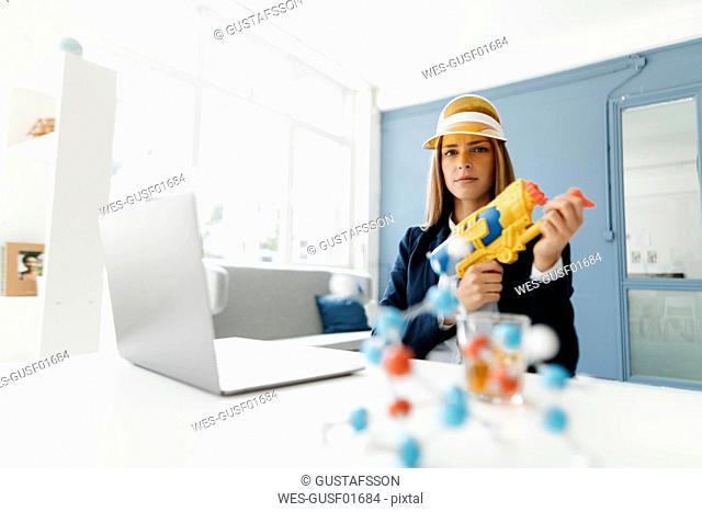 Female scientist holding water gun, studying molecules