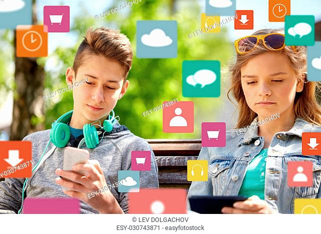 technology, internet and people concept - teenage boy with smartphone and headphones and girl with tablet pc computer outdoors over virtual icons