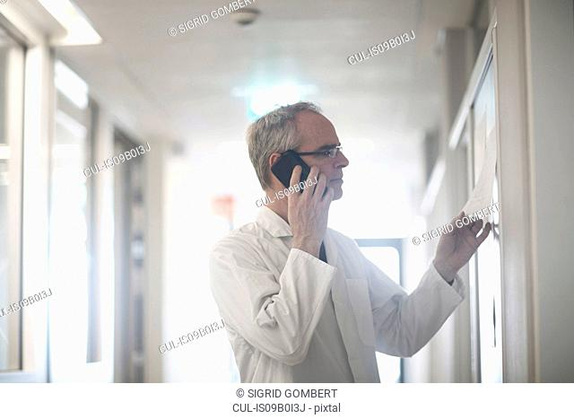 Male meteorologist reading charts and talking on smartphone in weather station laboratory