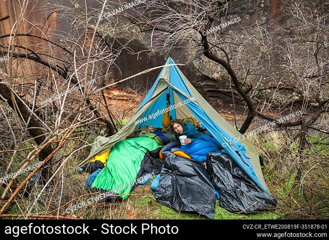 Campers emerge from tent after rain near Escalante River, Utah