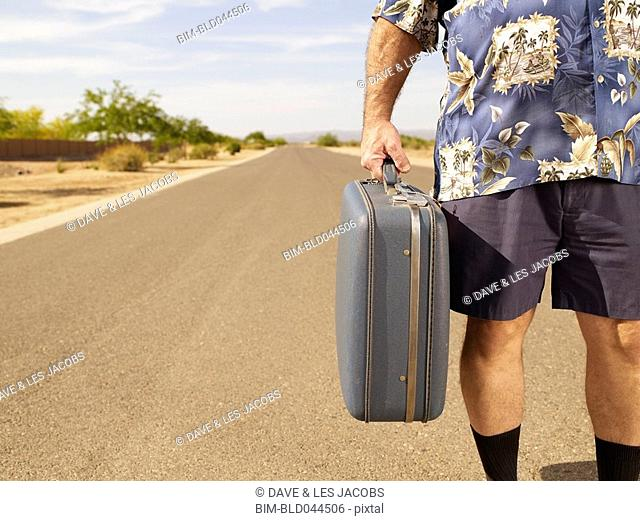 Senior Mixed Race man holding suitcase