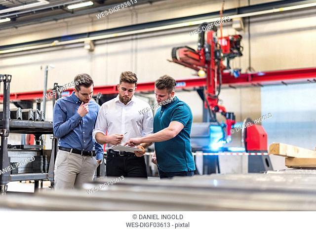 Three men sharing tablet on factory shop floor
