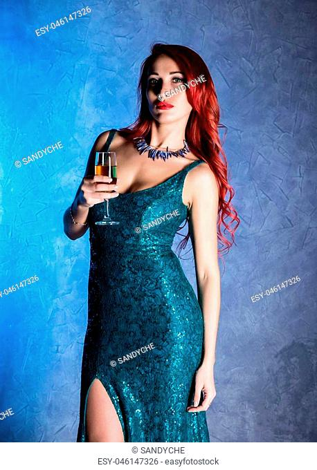 Young sexy woman with big boobs in blue elegant dress holding wineglass with champagne