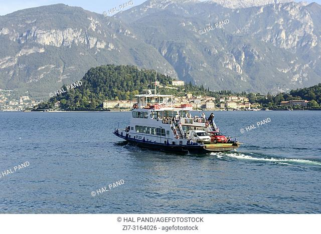 CADENABBIA, ITALY - OCTOBER 03: fall sun lightens ferry boat crossing lake at historical touristic village on Lario lake, shot in bright fall light on oct 03