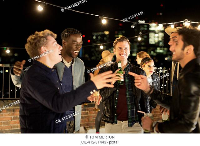 Young men drinking and laughing at rooftop party