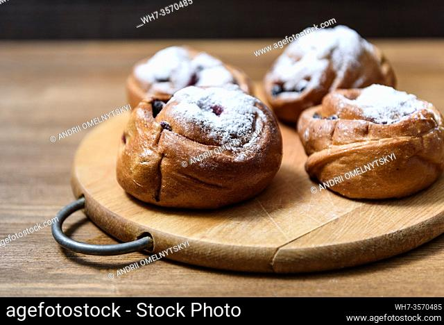 bun with currants covered with powdered sugar lay on a chopping board brown