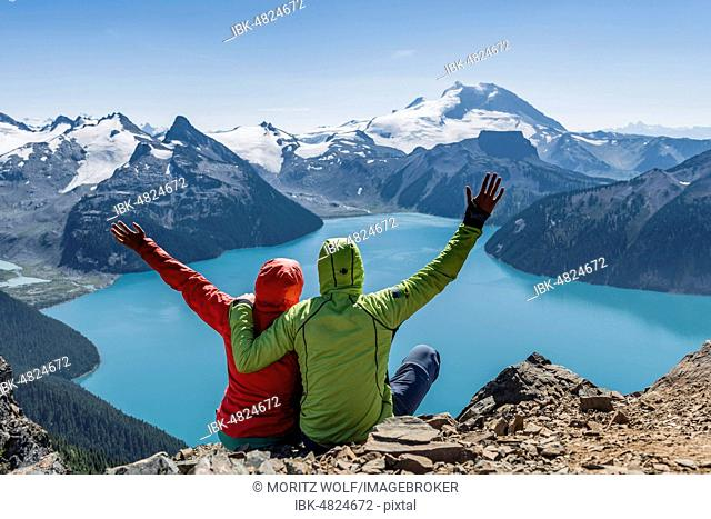 View from the Panorama Ridge hiking trail, two hikers sitting on a rock stretching arms in the air, Garibaldi Lake, turquoise glacial lake